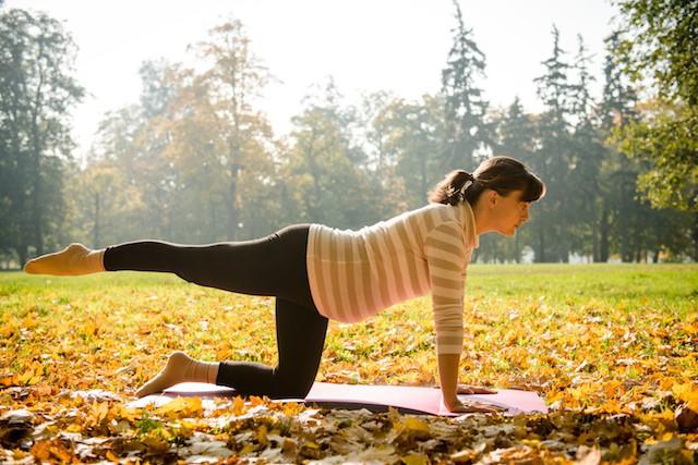 gravid kvinne trener utendørs