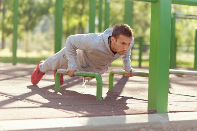 mann som gjør push ups fra stang