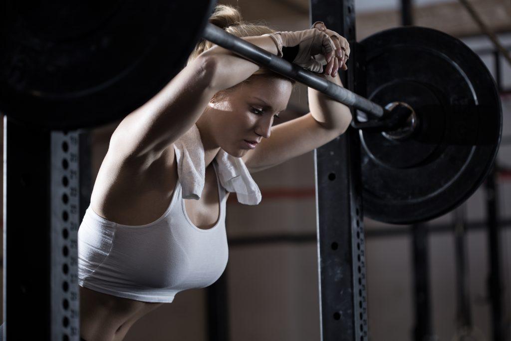 styrketrening der kvinne er sliten over vektstang