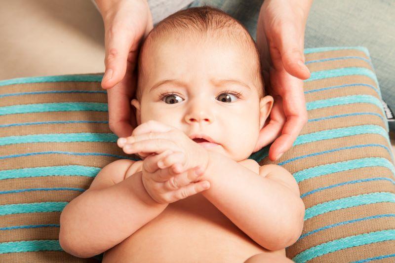 baby som får kiropraktorbehandling av nakke